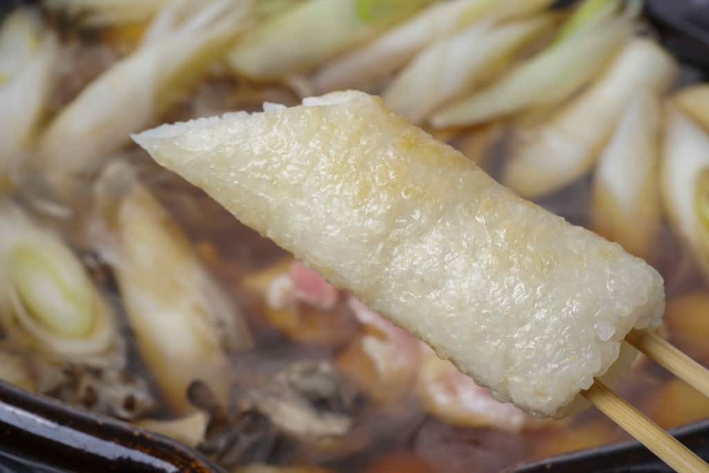 具材とスープが入った土鍋にきりたんぽを入れる、箸でつまんだきりたんぽと土鍋