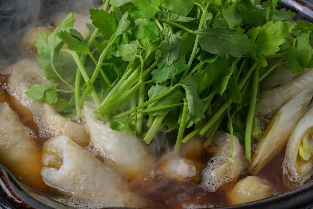 きりたんぽ・比内地鶏・スープが入った土鍋にたっぷりのセリを入れる、佐田商店のきりたんぽ鍋