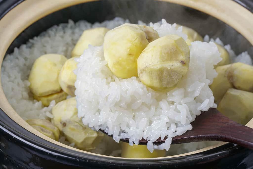 土鍋の中の栗ごはんをしゃもじですくう、丹波栗の炊きたてご飯をしゃもじですくう