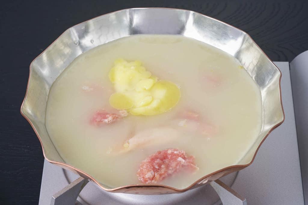 コンロの上の銅鍋に水炊き用のスープと鶏もも肉とつみれを入れる、博多とり田の水炊きスープ