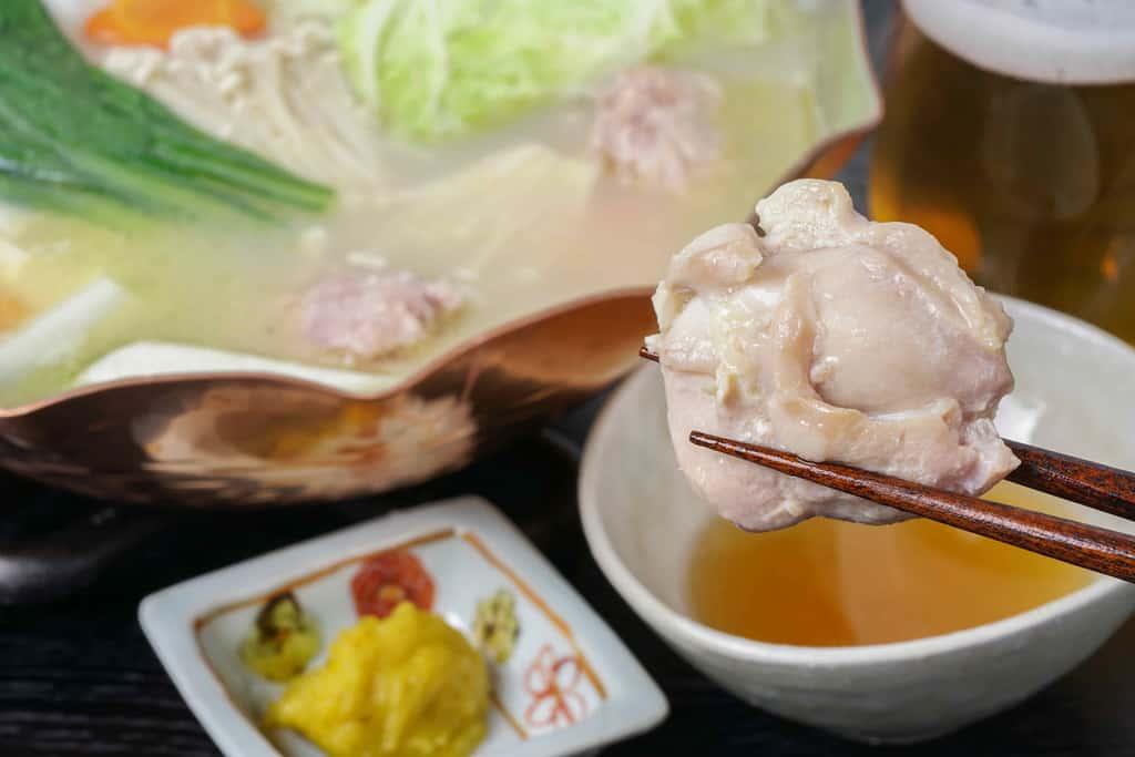 水炊きの入った銅鍋・ビール・柚子胡椒・ポン酢・箸でつまんだ鶏モモ肉、博多とり田の水炊き鍋を食べる