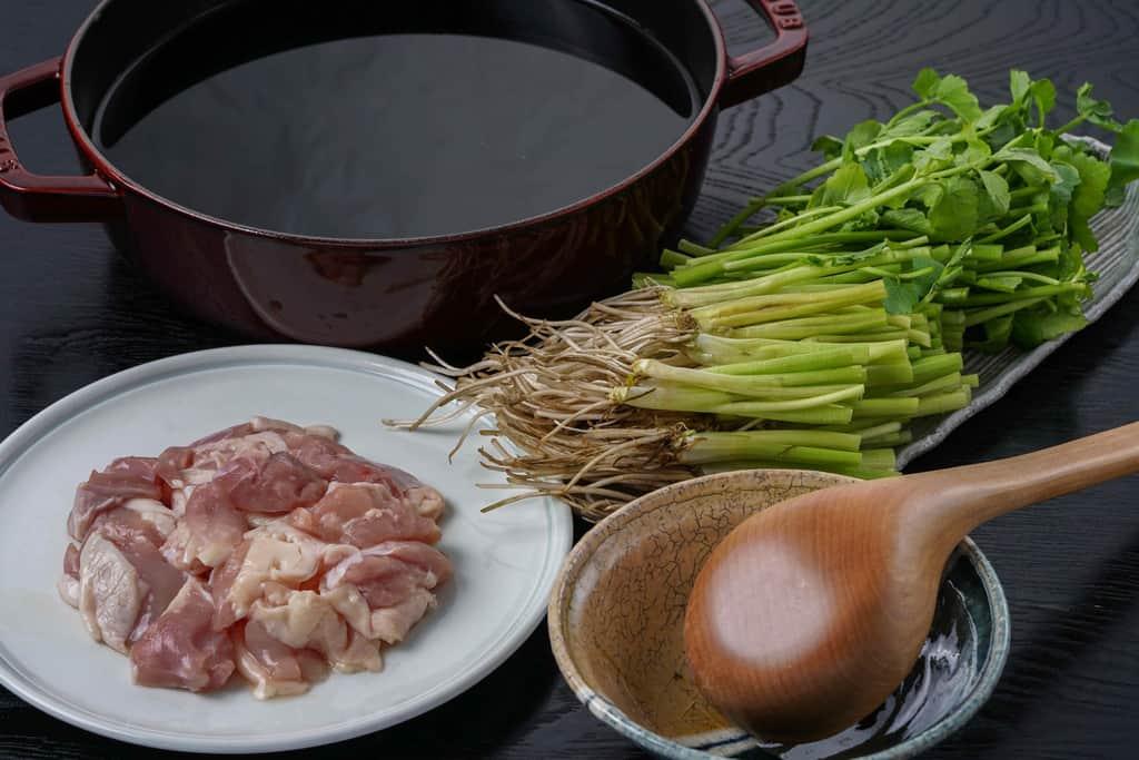 梵天食堂のせり鍋セットの具材とスープ、せせり・鶏もも肉・ストウブ鍋に入ったスープ
