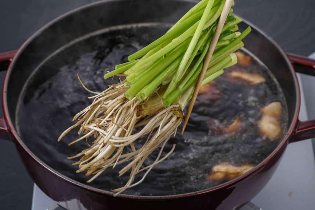 せりを箸でつまみストウブ鍋の中で沸騰するスープに入れる、梵天食堂せり鍋セットのせりを箸でつまんで鍋に入れる