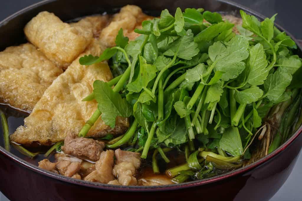 せり鍋の中に揚げを入れる、ストウブ鍋で煮込む仙台名物のせり鍋