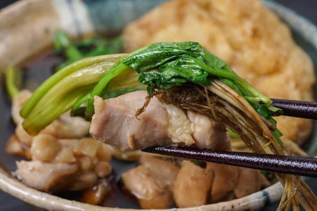 箸でセリ鍋の具材をつまむ、鶏もも肉・せりを箸でつまむ
