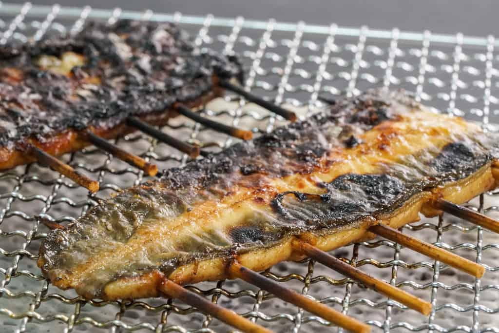 こんがりと焼けた皮を上にして網の上で焼くうなぎの蒲焼き