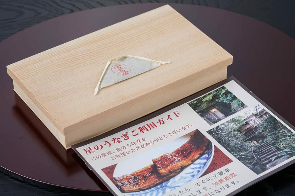 木目の入れ物に入った星のうなぎの「うなぎの蒲焼1人前」と山椒とパンフレット、通販うなぎの蒲焼き