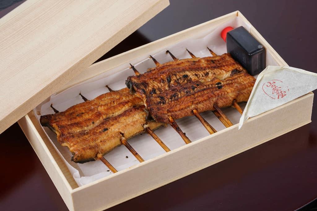 木製容器に入った星のうなぎの「うなぎ蒲焼1人前」とタレと山椒、木製容器の中には竹串が刺さった状態の2切れのうなぎ蒲焼き