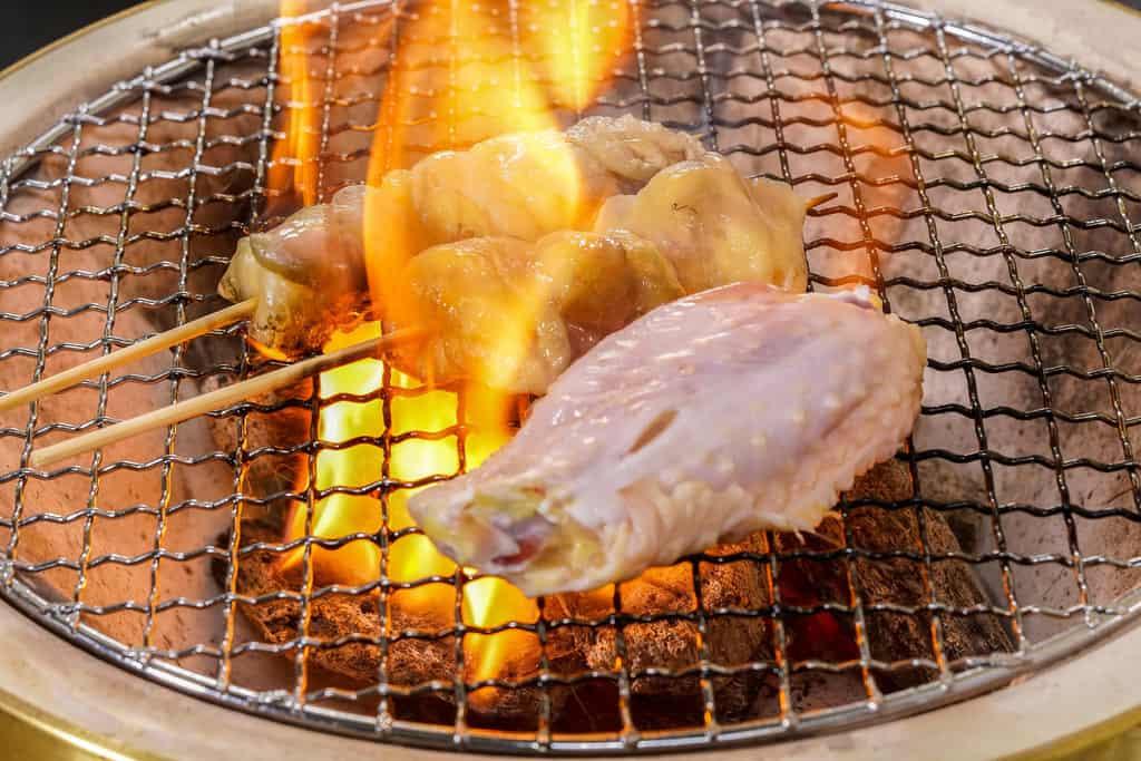 炎が立ち上る炭火焼き鳥、七輪の網の上で炎に包まれた淡海地鶏の手羽先・骨付ぼんじり・皮