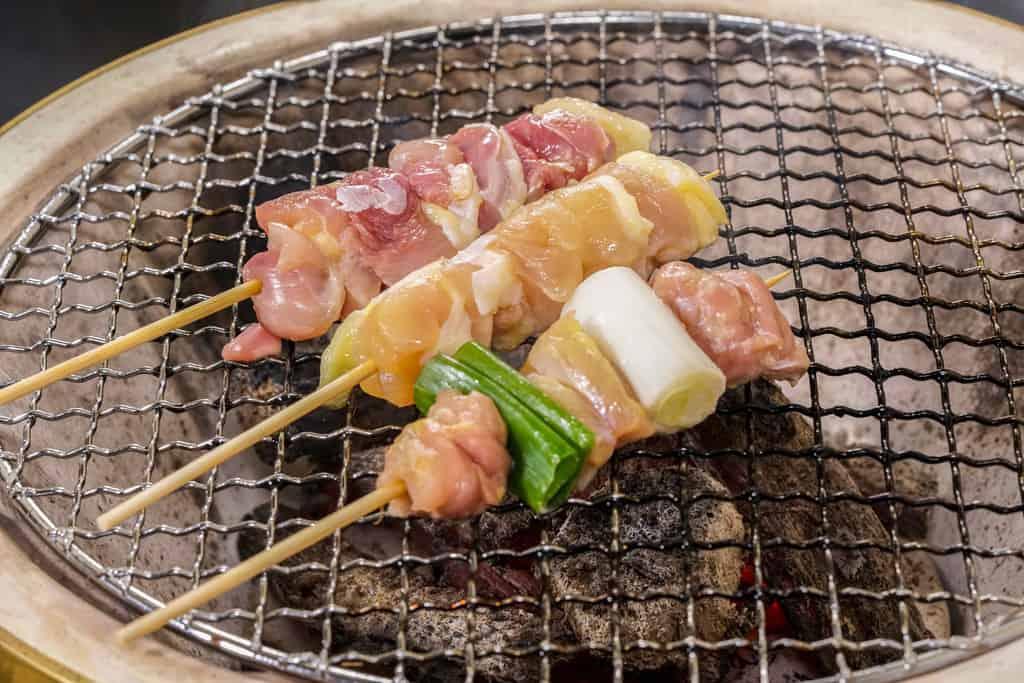 七輪の網の上に並べたかしわの川中の淡海地鶏の生串(ねぎま・手羽元・モモ肉)、地鶏の炭火焼き鳥