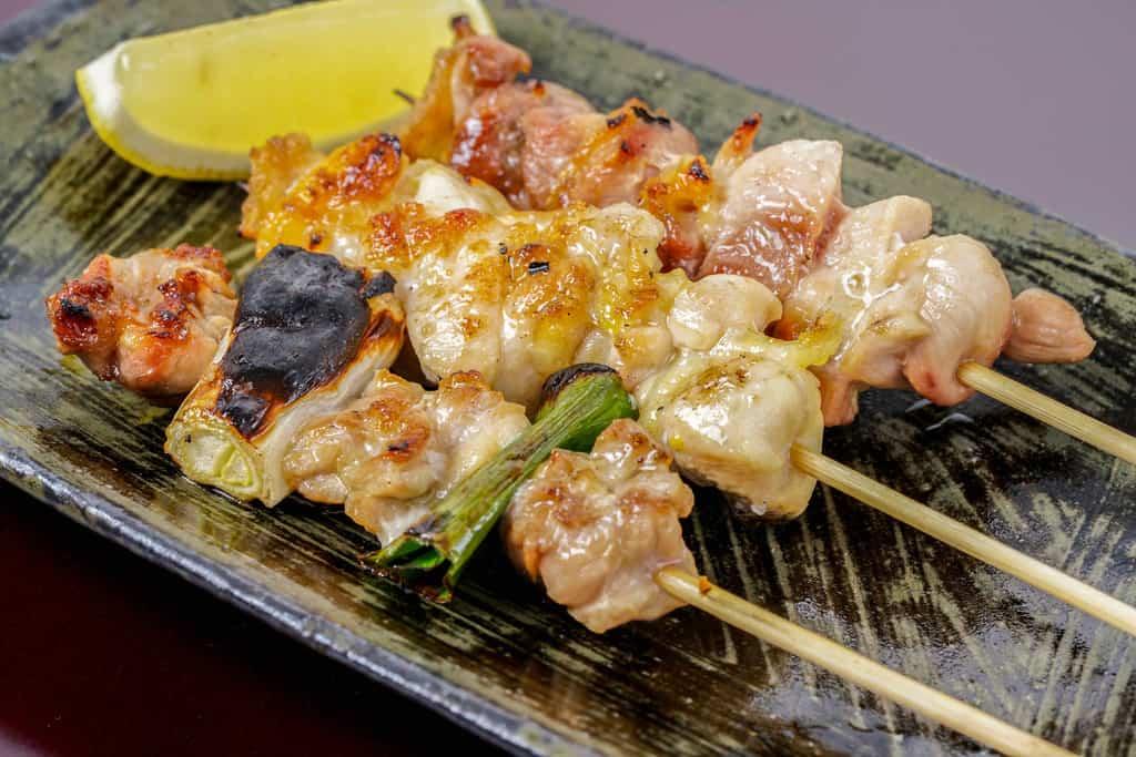 炭火で焼いた淡海地鶏のねぎま串・モモ串・手羽元串を皿に並べてレモンを添える、焼き鳥の盛り合わせ