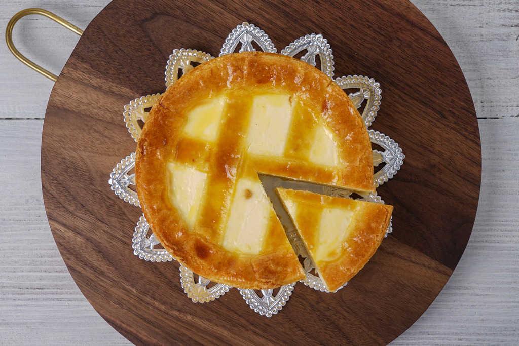 カッティングボードの上のトロイカのベークド・チーズケーキ、カッティングボードの上でワンピース切り分けられたベークド・チーズケーキ