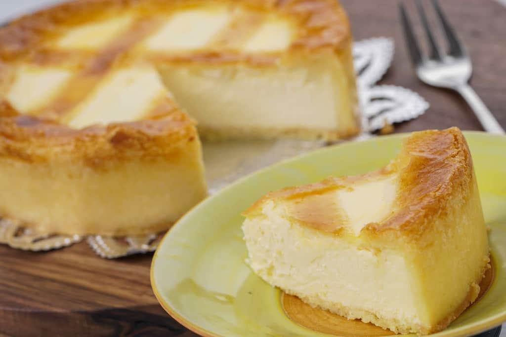 皿に乗ったワンピースのベークド・チーズケーキとカッティングボードに乗ったホールのベークド・チーズケーキ