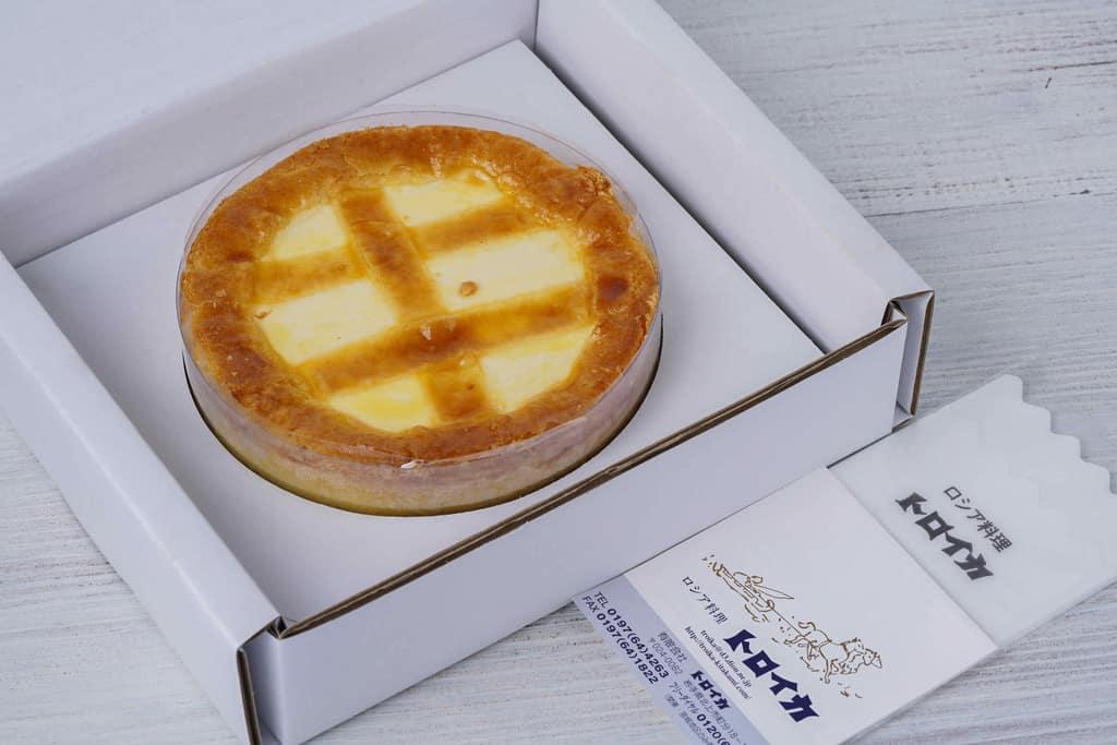 岩手県のロシア料理とチーズケーキの店トロイカのベークド・チーズケーキ5号の箱の中身、箱に入ったトロイカのベークド・チーズケーキとリーフレットとテーブルナプキン