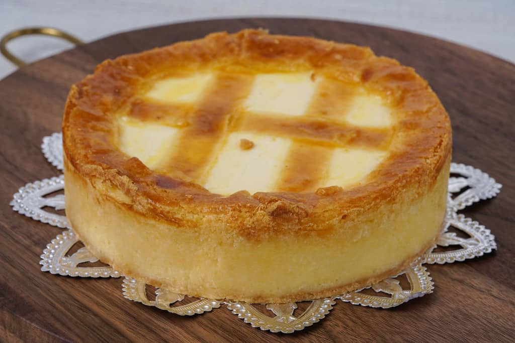 丸いカッティングボードの上に乗ったトロイカのベークド・チーズケーキ