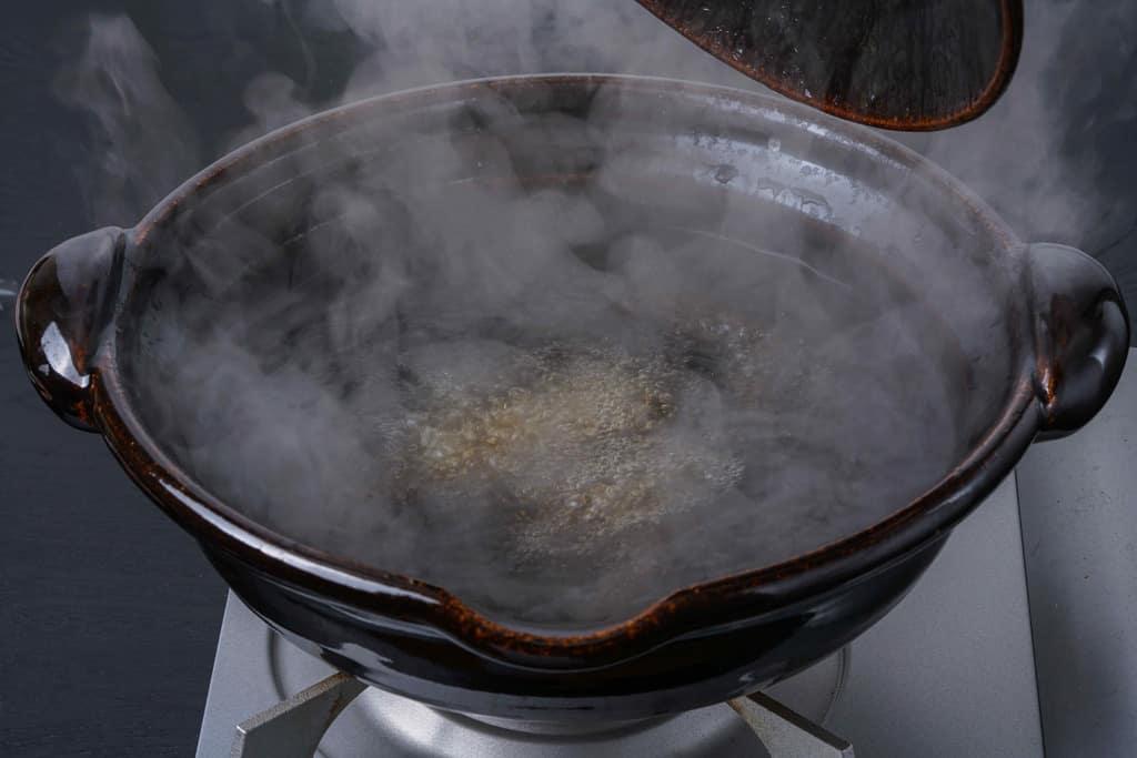 土鍋の中の鴨鍋用のスープが沸騰して湯気がでる