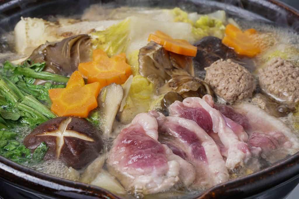 土鍋の中で軽く火が通った状態の合鴨ロース肉と合鴨ミンチや野菜・豆腐、鴨重の鴨鍋うどん