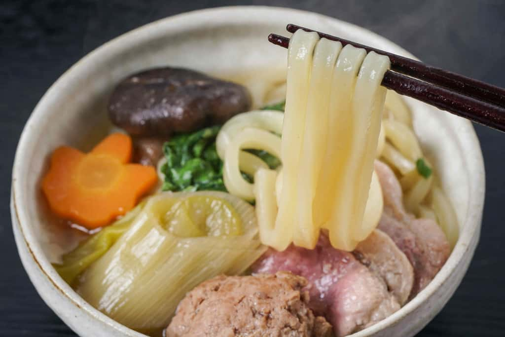器に入ったうどん・ネギ・椎茸・鴨ロース肉・鴨肉ミンチ・人参、うどんを箸で持ち上げる