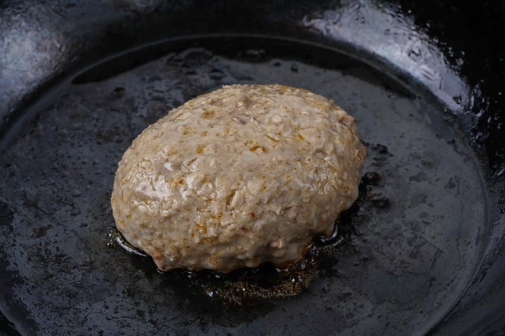 鉄フライパンの上で焼くいきや食品の唐津バーグ、鉄フライパンでハンバーグを焼く