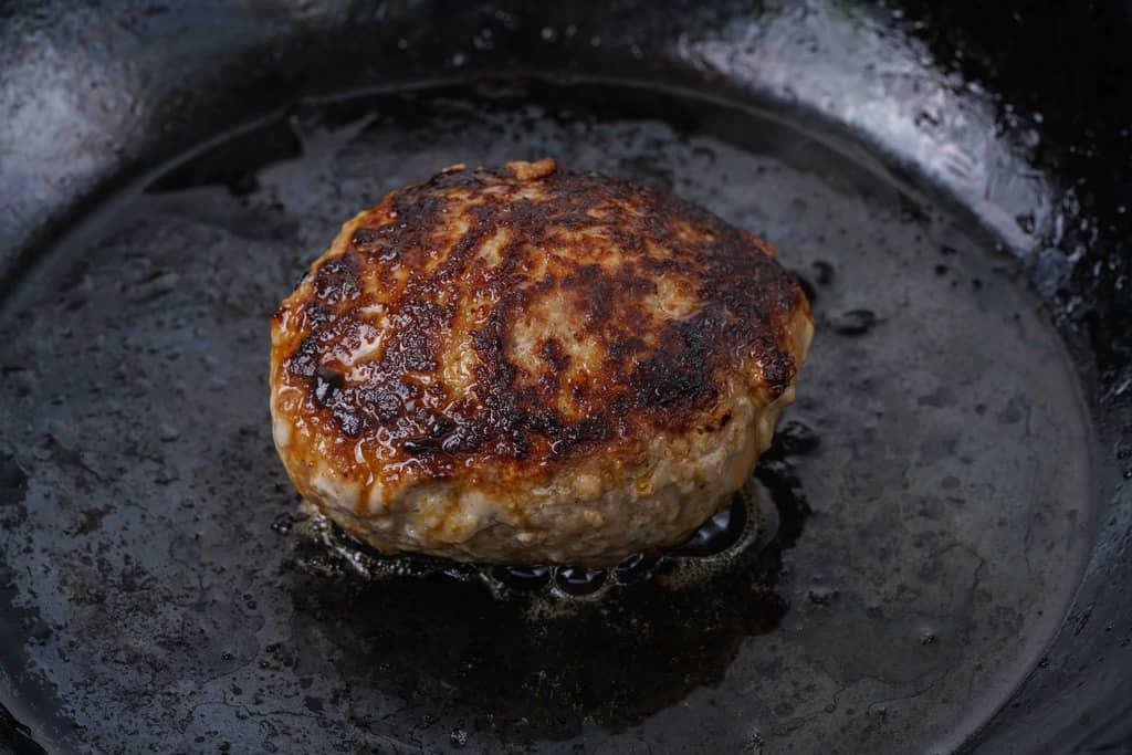 鉄フライパンの上で表面がこんがりと焼きあがったいきや食品の唐津バーグ1個、鉄フライパンで焼いたハンバーグ