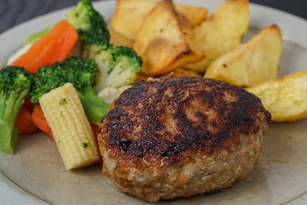 付け合わせのフライドポテトと野菜と共に皿に盛り付けたいきや食品の唐津バーグ、ブロッコリー・人参・コーン・フライドポテト・ハンバーグ