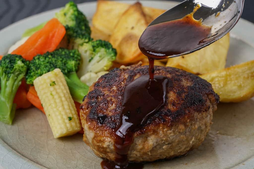 皿に盛り付けたいきや食品の唐津バーグにソースをかける、焼いたハンバーグにスプーンでソースをかける