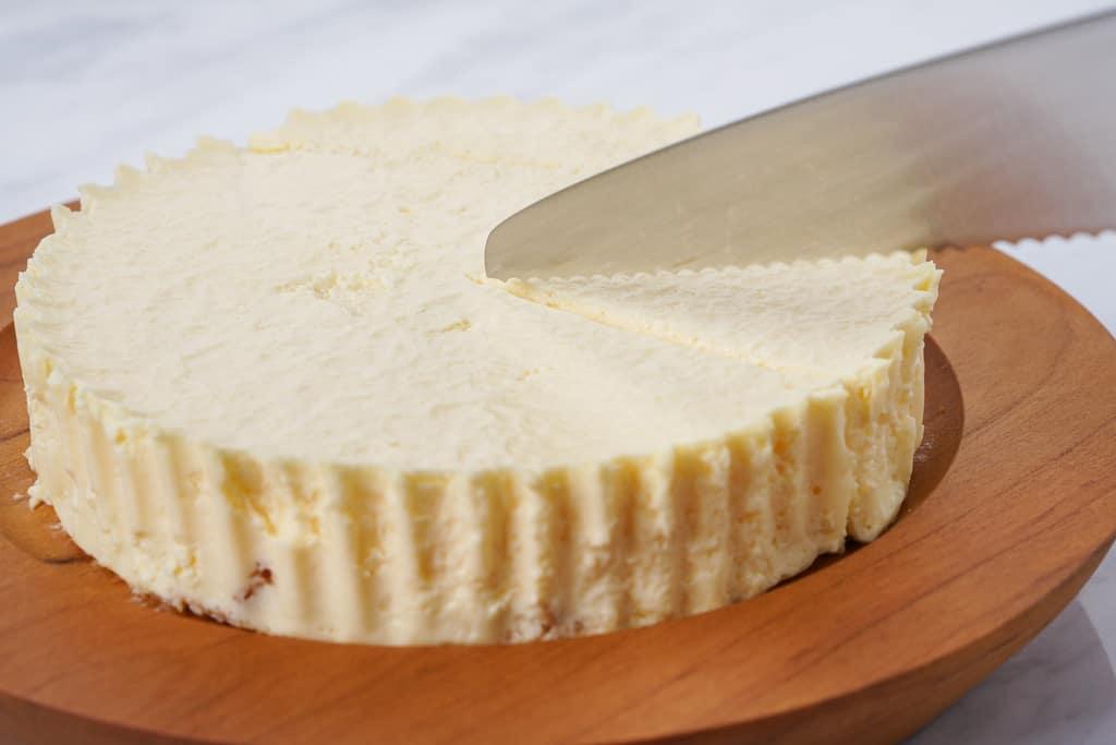 カッティングボードの上に乗った小岩井農場のレアチーズケーキをナイフでカットする