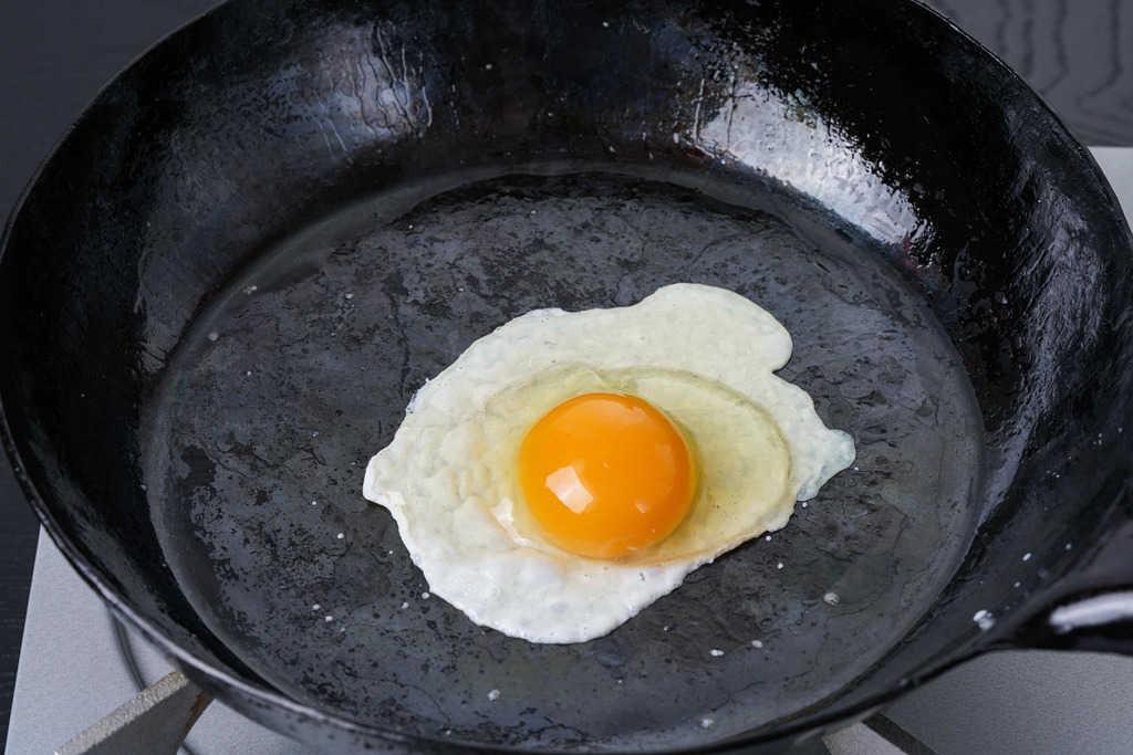 フライパンの上の小岩井農場たまごの生卵、フライパンで目玉焼きを作る