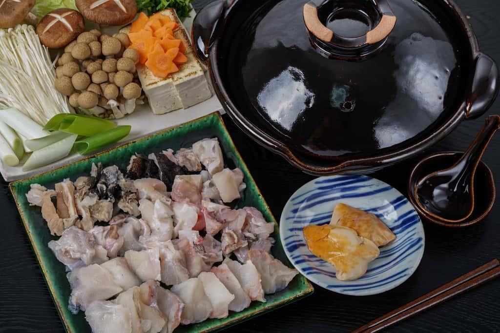 鍋で煮込む前のあんこう鍋用の具材、きあんこうの身・あら・皮・あん肝・土鍋・白菜・春菊・人参・ネギ・しいたけ・えのき・しめじ・豆腐