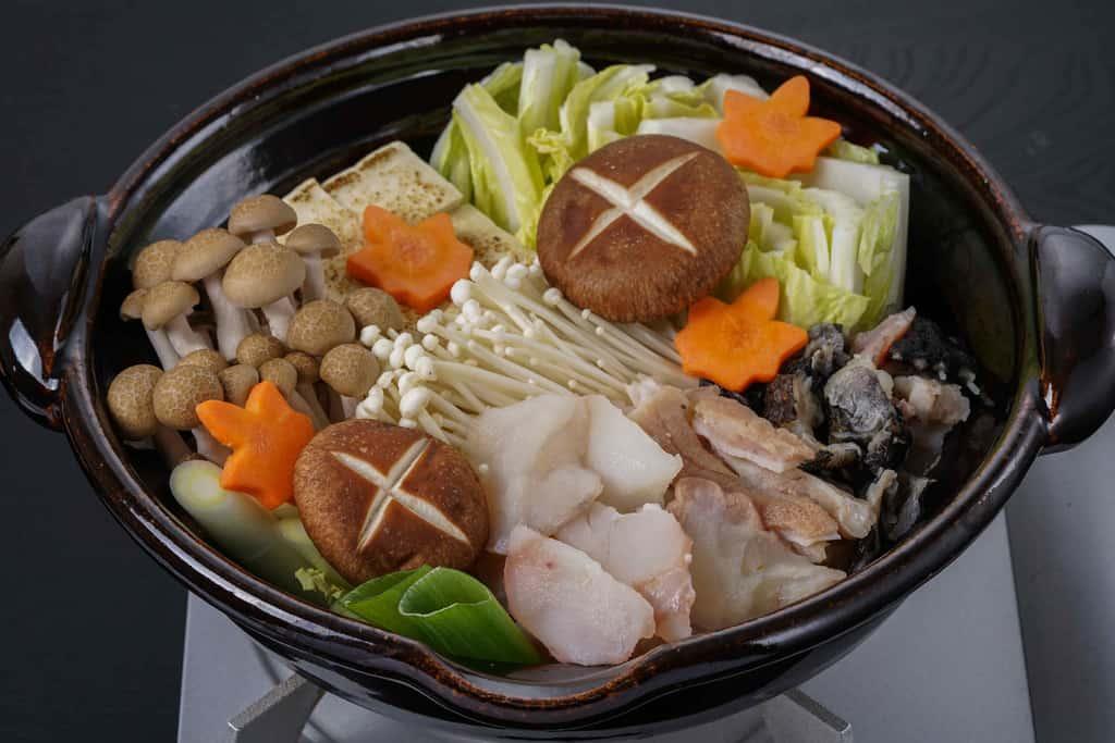 土鍋の中にあんこう鍋用の具材を入れる、煮込む前のあんこう鍋