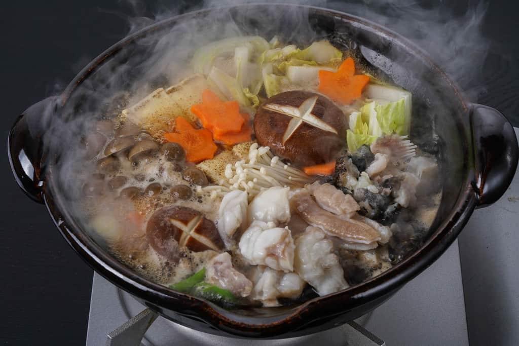 湯気がでる土鍋の中のあんこう鍋、駒嶺商店のきあんこう鍋の具材と野菜を土鍋で煮込む