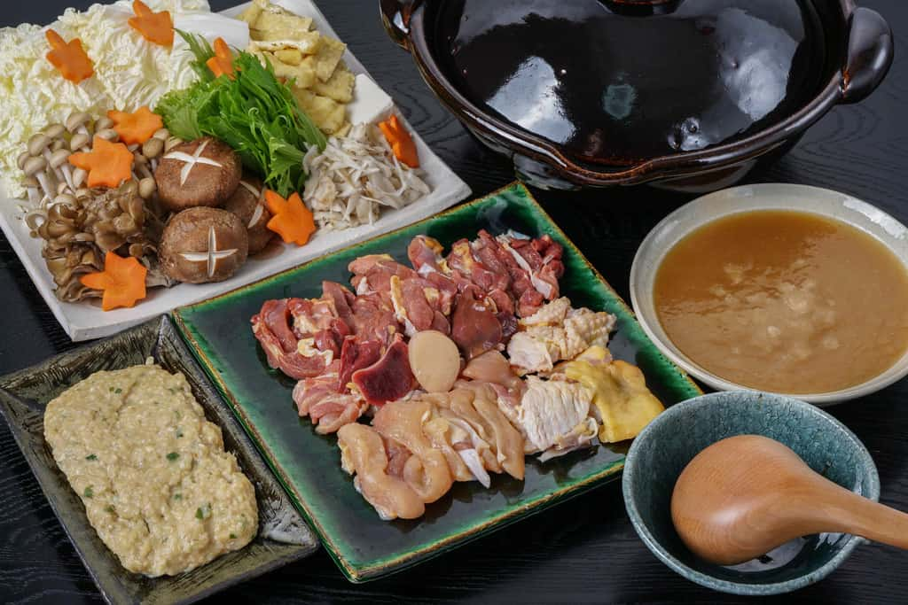 とり鍋料理の具材を並べる、野菜類・きのこ・土鍋・地鶏のミンチ・近江地鶏の肉・地鶏スープ