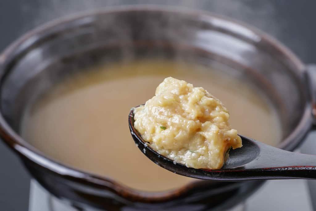 土鍋の中で煮立ったスープにレンゲに乗せた地鶏ソフト味付けミンチを入れる