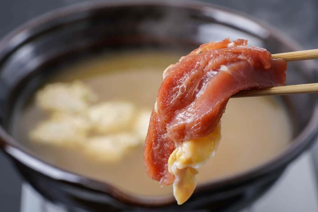 土鍋の中で煮立ったスープに近江しゃものモモ肉を入れる