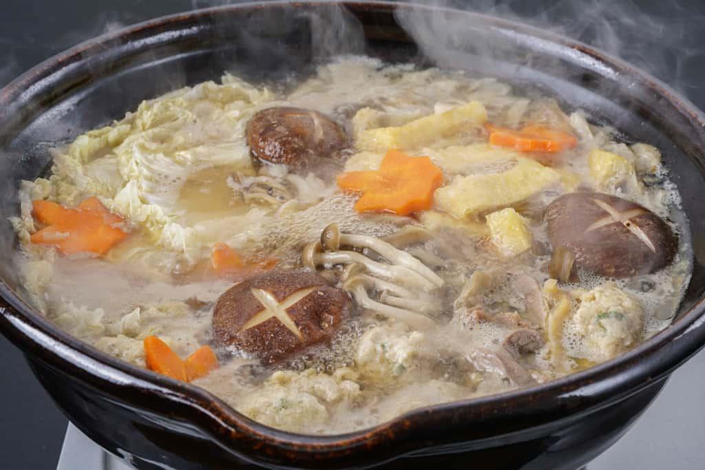 湯気の立つ鍋で煮込んだかしわの川中の近江しゃものとり鍋、鍋料理