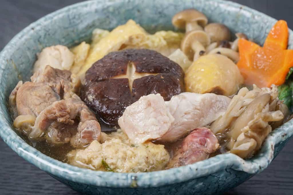 土鍋で煮込んだ近江しゃも鍋の具材が入った小鉢、とんすいに入った地鶏鍋の具材