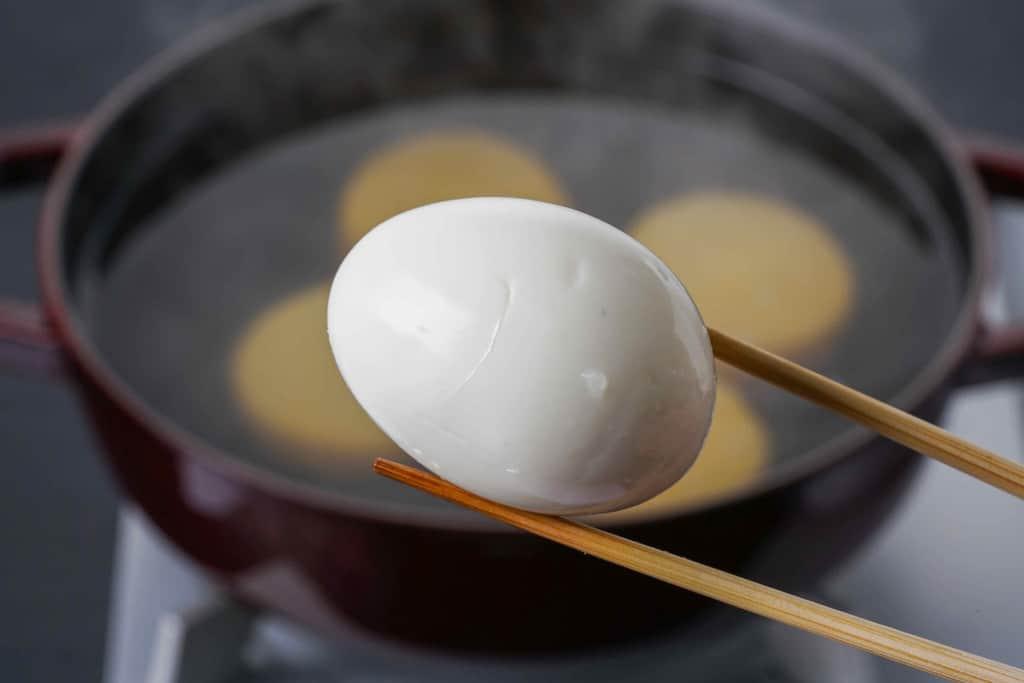 下鴨茶寮の京おでん鍋用の玉子を箸でつまんで鍋に入れる