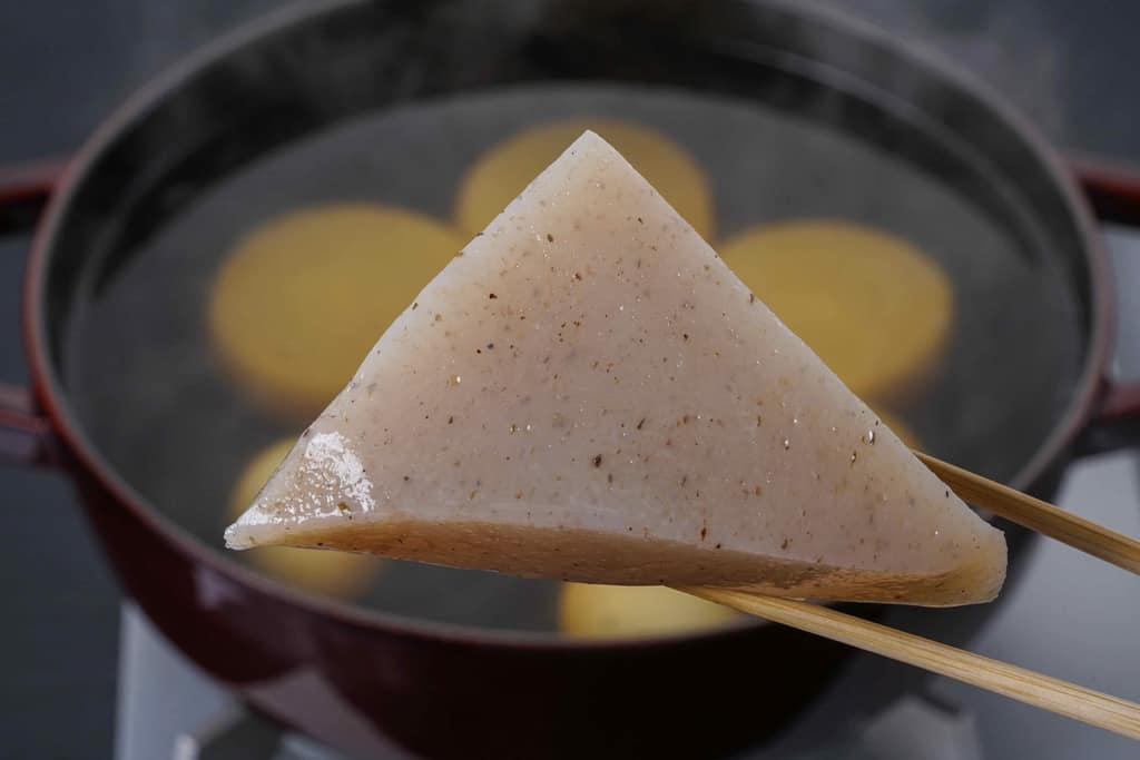 下鴨茶寮の京おでん鍋用のこんにゃくを箸でつまんで鍋に入れる