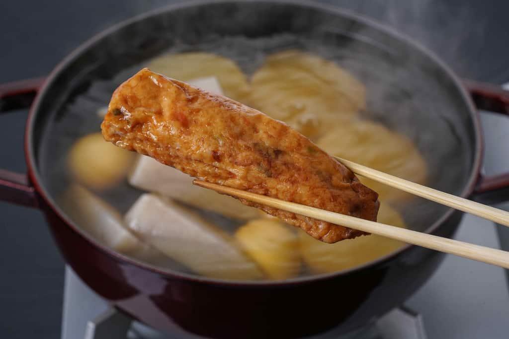 下鴨茶寮の京おでん鍋用のとりつくね天を箸でつまんで鍋に入れる
