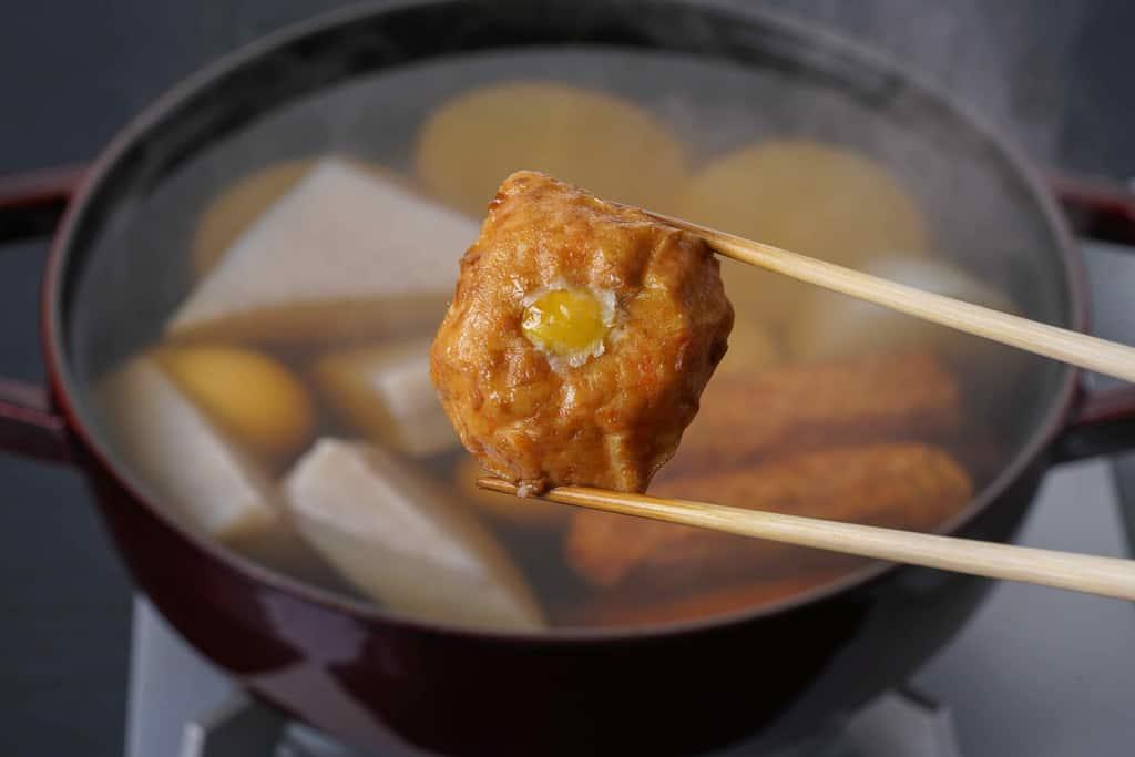 下鴨茶寮の京おでん鍋用の京ひろうすを箸でつまんで鍋に入れる