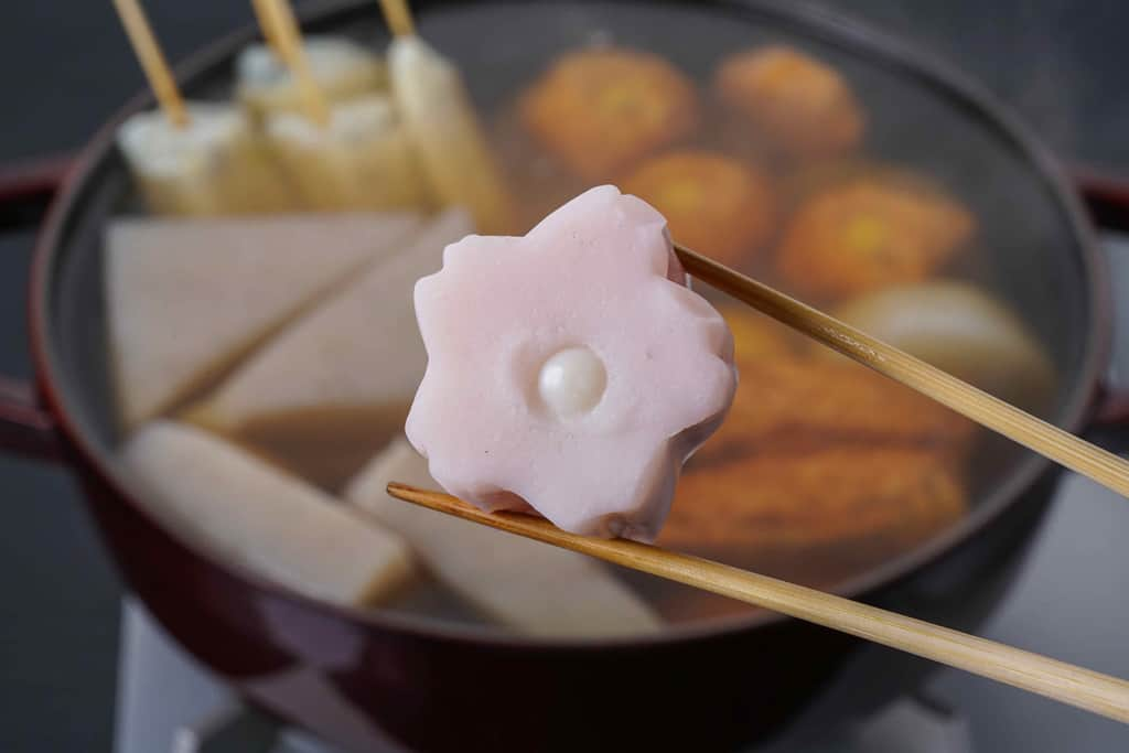 下鴨茶寮の京おでん鍋用の小梅を箸でつまんで鍋に入れる