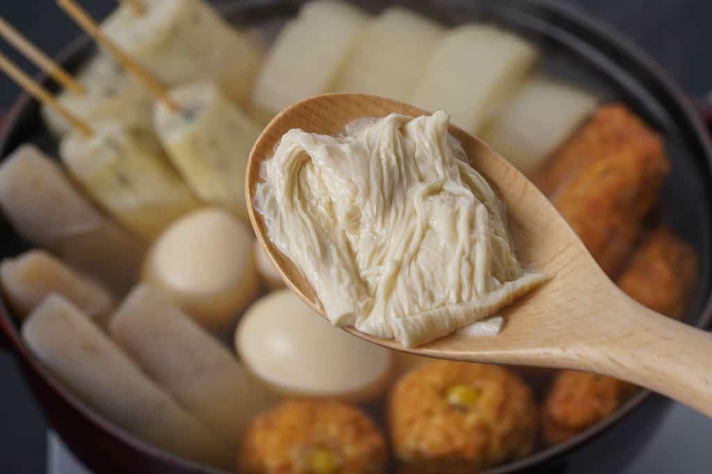 下鴨茶寮の京おでん鍋用の生湯葉を木のスプーンに乗せて鍋に入れる