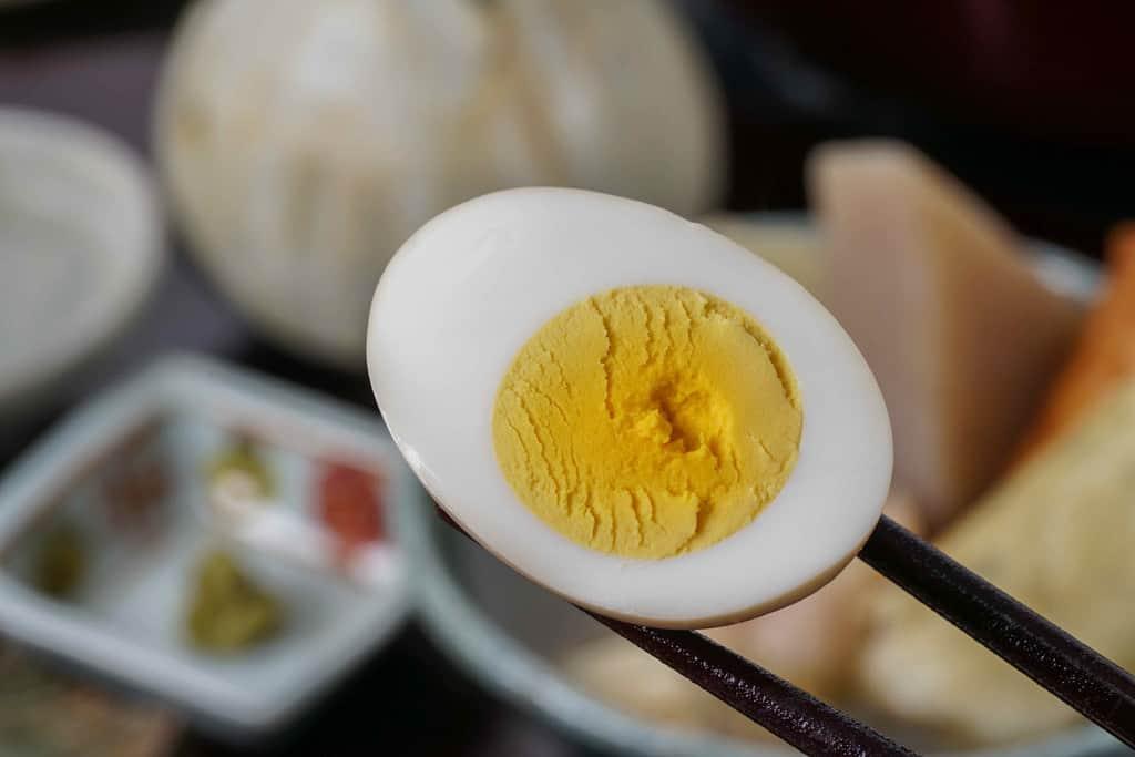 下鴨茶寮の京おでんの玉子を半分に割って箸でつまむ