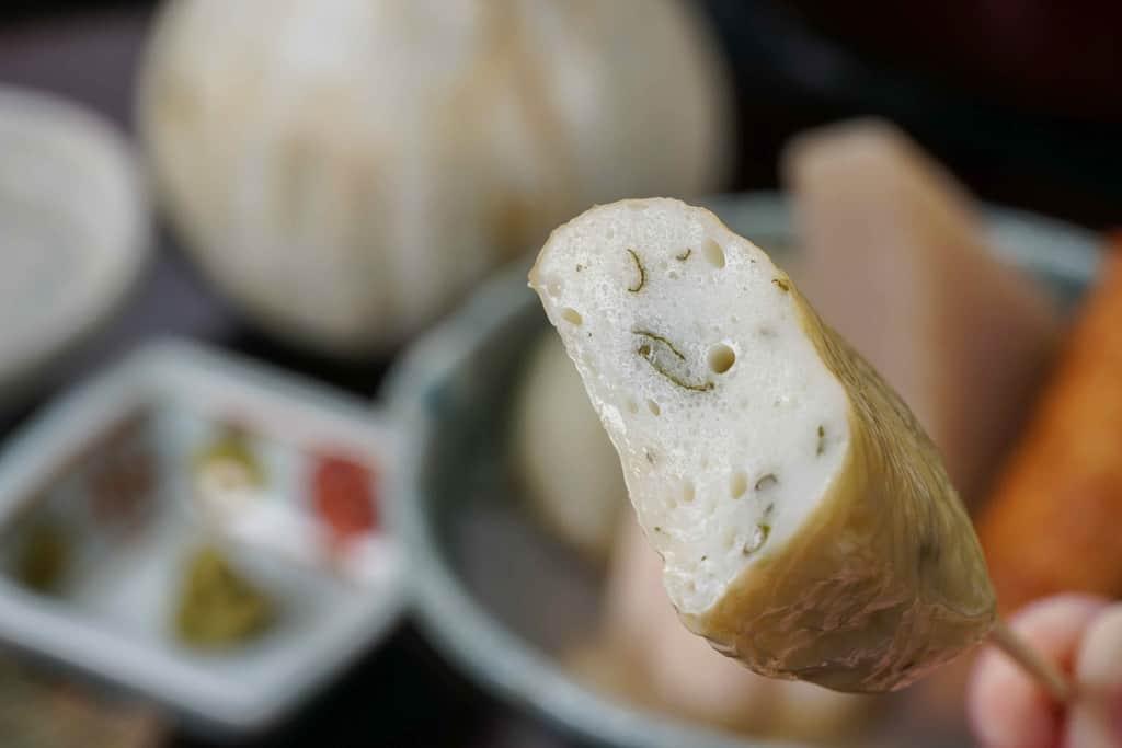 下鴨茶寮の京おでんの湯葉巻きを半分にカットして箸でつまむ