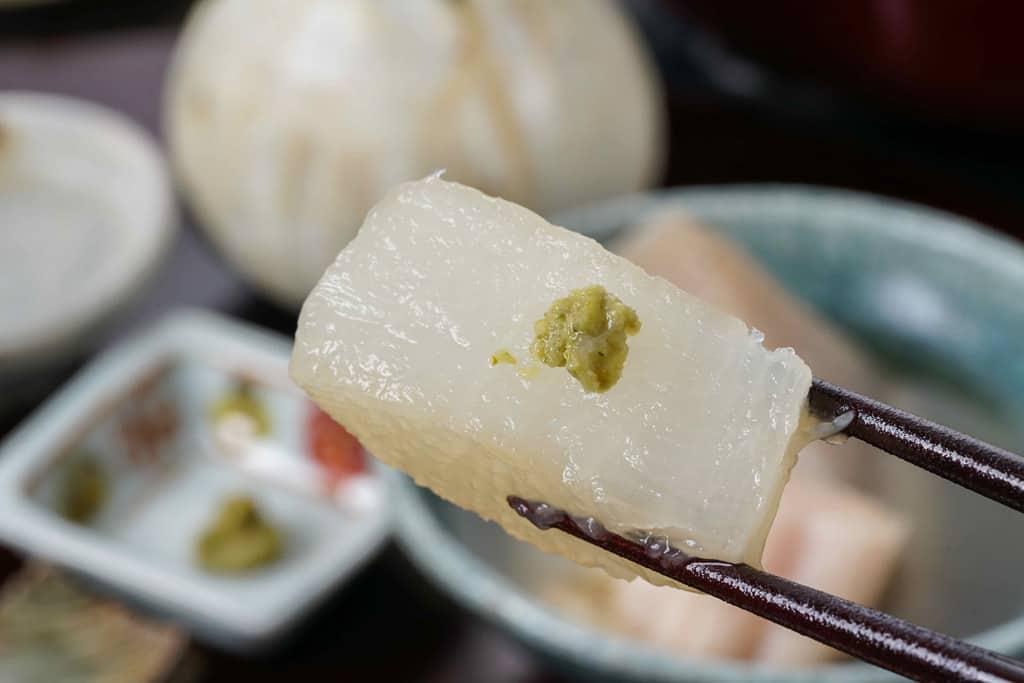 下鴨茶寮の京おでんの大根を箸でつまんで柚子胡椒をのせる