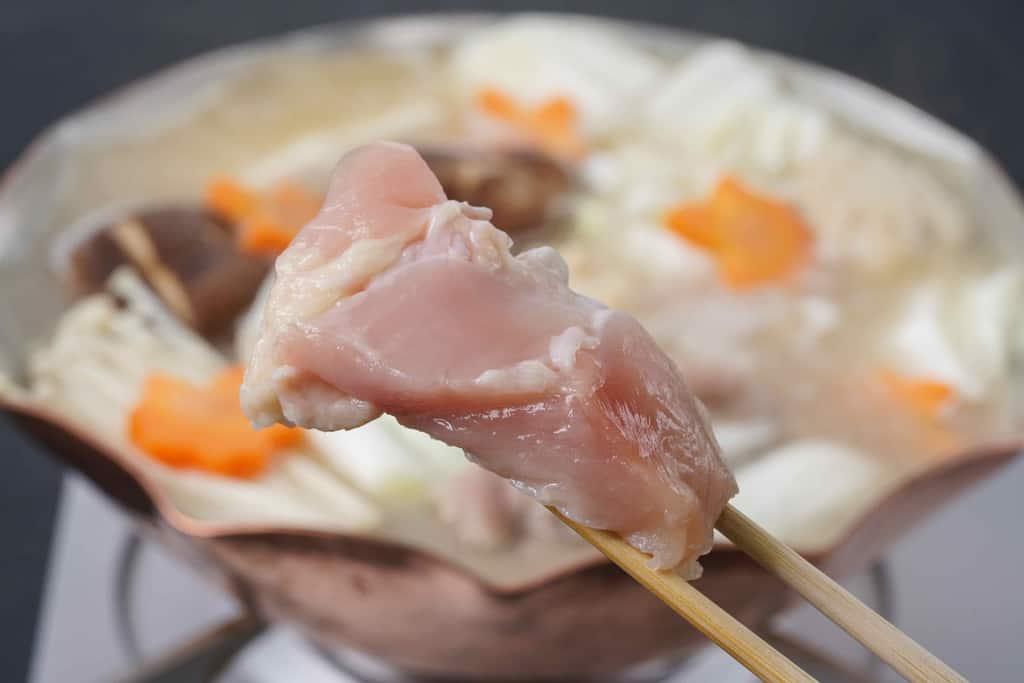 銅鍋の中で煮立っている具材が入った水炊き鍋の中に名古屋コーチンのむね肉を入れる