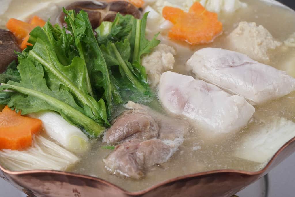 銅鍋の中の名古屋コーチン水炊き鍋、銅鍋で調理する水炊き鍋