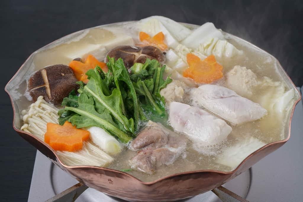 銅鍋の中で湯気がたつ名古屋コーチンの水炊き鍋、完成した三和の純鶏名古屋コーチン水炊き鍋