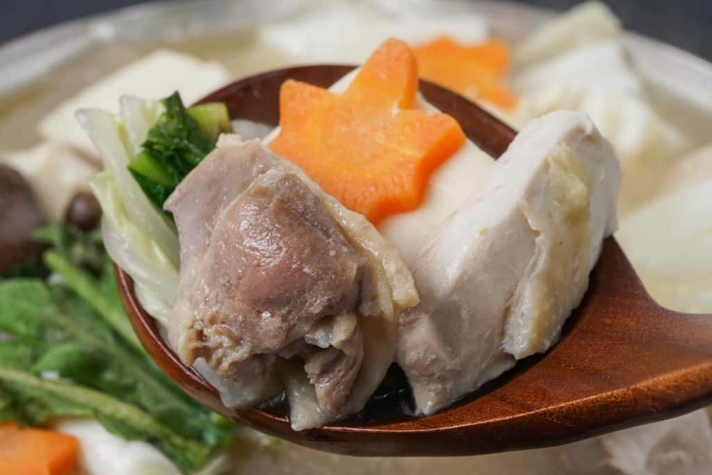 銅鍋の中の名古屋コーチン水炊き鍋の具材を杓子で取り分ける