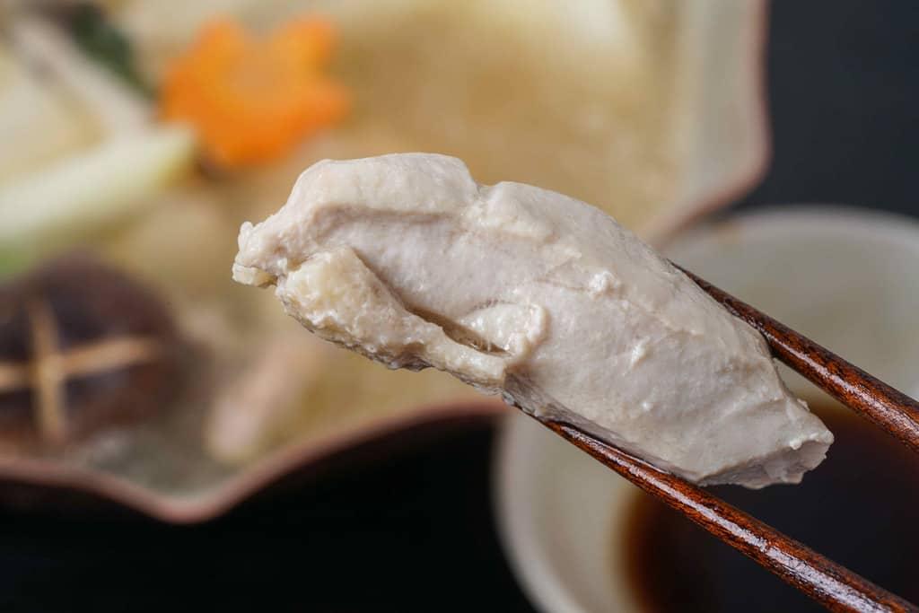 箸で持ち上げた水炊き鍋の名古屋コーチンむね肉